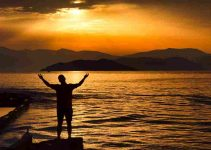 Man raising hands in front of body of water