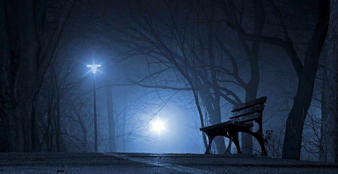 A lonely park bench in night fog